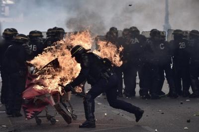 Париж. Полицейские пытаются сбить пламя с тележки, которую толкнули в их сторону.